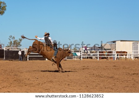 A cowboy competing in a bull riding event at an Australian country rodeo