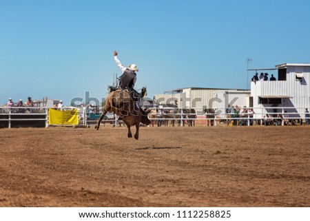 A cowboy competing in the bullriding event at a country rodeo