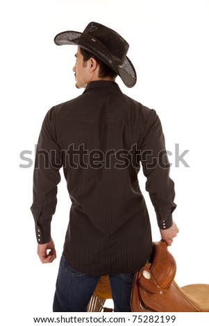 A cowboy from the back.  He is holding a saddle.