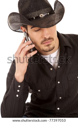 A cowboy has his eyes closed and a phone.