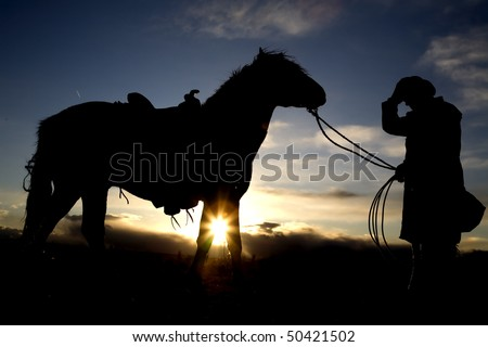 A cowboy holding onto his hat and his horse - stock photo