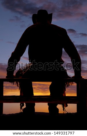 A cowboy in the sunset sitting on a fence.