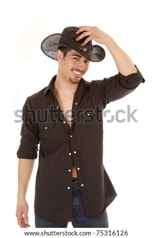 A cowboy is dressed in black holding his hand on his hat.