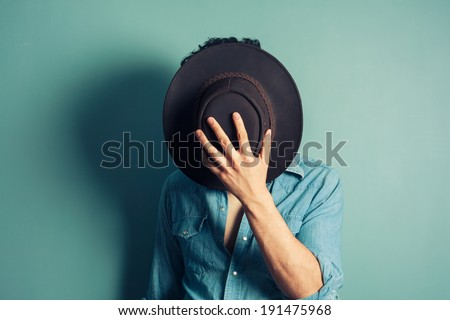 A cowboy is hiding behind his hat