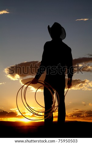 A cowboy is holding a rope in the sunset.