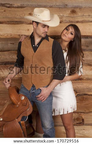 A cowboy is holding a saddle and looking back at an Indian.
