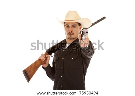 A cowboy is holding two guns.  A shotgun over his shoulder and a pistol pointing in his other hand.