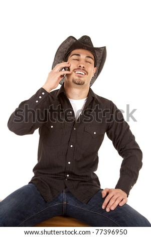 A cowboy is laughing and talking on his phone.