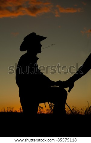 A cowboy is on his knee with a womans leg on him in the sunset.