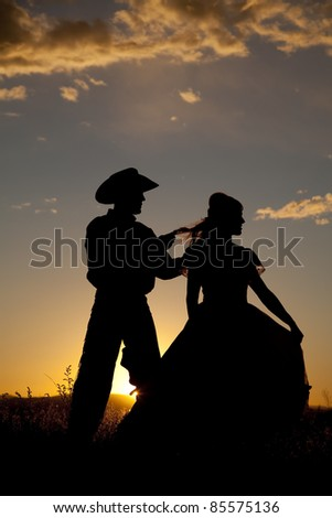 A cowboy is playing with a woman's hair in the sunset.
