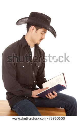 A cowboy is reading a book on a bench. - stock photo