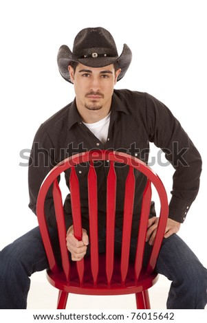 A cowboy is sitting on a red chair with a serious expression.