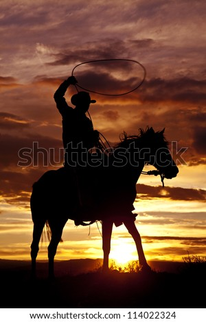 A cowboy is sitting on his horse in the sunset and swinging a rope.