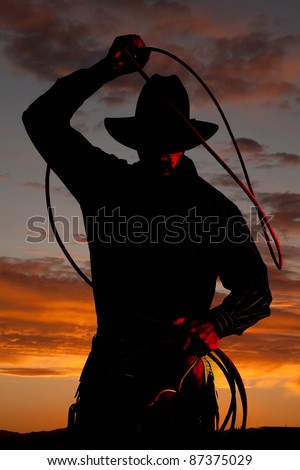 A cowboy is standing in the sunset with a rope. - stock photo