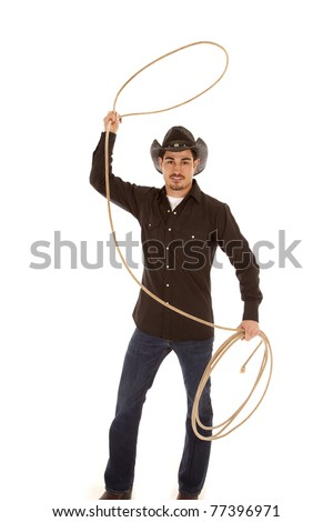 A cowboy is standing with a rope in his hand.