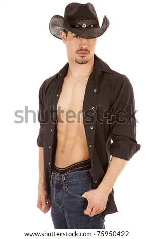A cowboy is standing with a serious expression and his shirt open.
