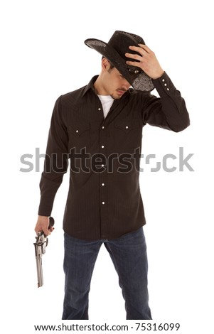 A cowboy is standing with his hand on his hat and a gun in the other hand.