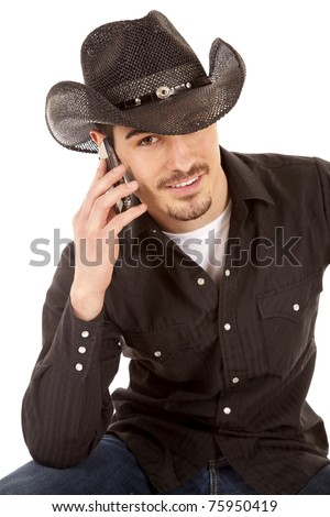 A cowboy is talking on the phone and smiling.