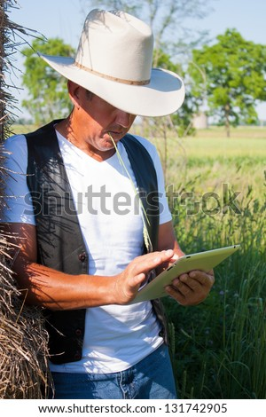 A cowboy leaning on the hay stack in a countryside setting using touchscreen on a tablet computer