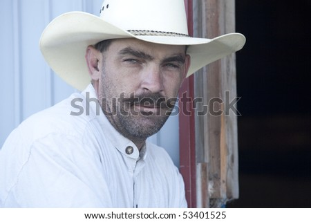 A cowboy leans up against a shed. - stock photo
