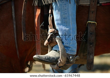A cowboy leg wearing jeans and a cowboy boot in a stirrup on a horse.