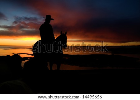 A cowboy on a hill against a sunset and ocean