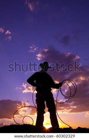A cowboy silhouetted in the sunset with a rope.