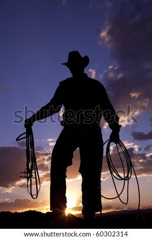 A cowboy  silhoutted by a beautiful sunset holding a rope and a halter.