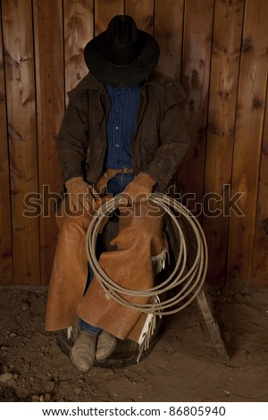 A cowboy sitting on a wine barrel with his head down.