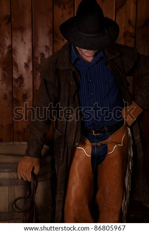 A cowboy standing next to a wine barrel with his fist on his hip holding his reins.