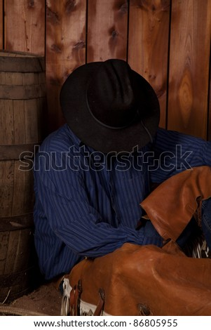 A cowboy taking a rest leaning his back on a wine barrel.