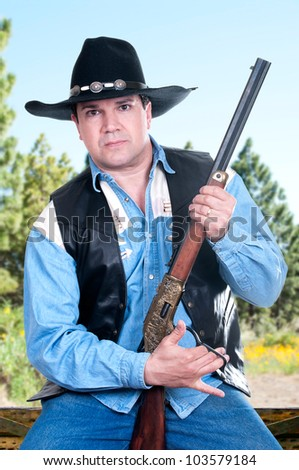 A cowboy with a serious expression on his face holding his rifle