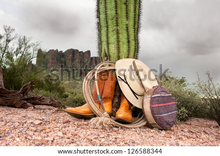 A cowboy wranglers boots, hat, lasso and canteen rest against a cactus in extreme, rugged desert terrain.