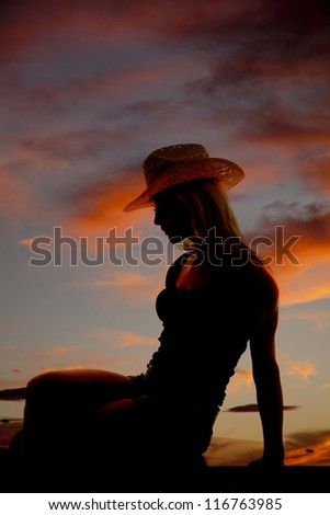 A cowgirl is sitting in the sunset as a silhouette.