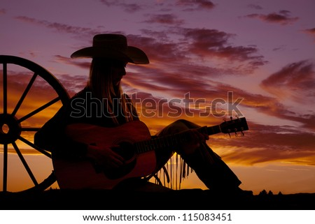 A cowgirl sitting up against a wagon wheel playing her guitar with the sunset behind her.