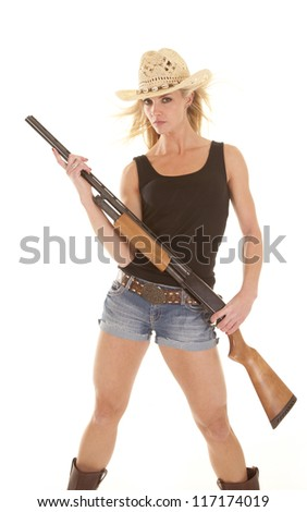 A cowgirl with a serious expression holding on to her rifle.