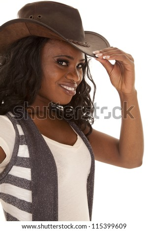 A cowgirl with a smile on her face looking at the camera and holding on to the brim of her hat.