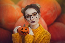 A cozy autumn photo of a girl with pumpkins in a yellow sweater and glasses. Stylish young woman in autumn decorations, in hands a Halloween pumpkin.