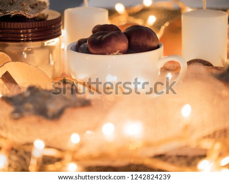 A cozy Christmas evening. Closeup of a mug with baked chestnuts, around a candle and garland