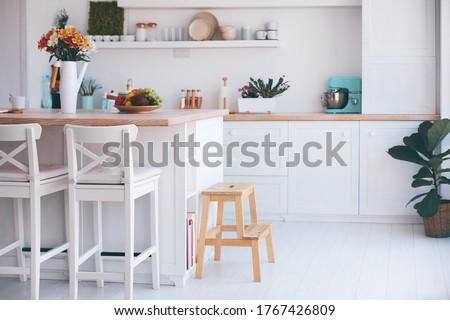 a cozy modern kitchen room interior with island counter, wooden furniture and wall shelves Stock photo ©