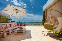 a cozy rooftop patio with wooden pallet furniture and hanging swing chair at sunny summer day