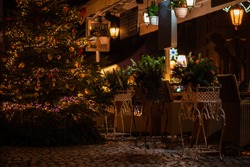 A cozy street cafe with Christmas decorations on the street of the old town in Prague. Christmas illumination. Bokeh garlands in the background. Christmas, winter, new year concept.