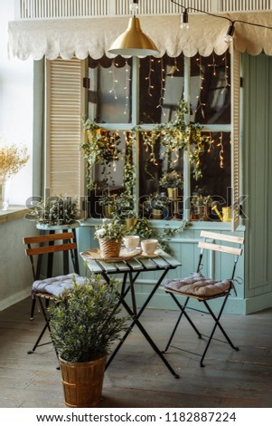A cozy summer café in the European style. The interior is in beige and green tones. Small wooden table and two chairs on the background of the window. The facade is decorated with live plants. #1182887224