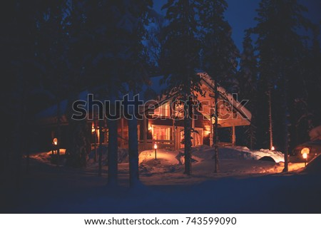 A cozy wooden cabin cottage chalet house covered in snow near ski resort in winter with the lights turn on, evening picture