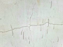 A cracked cement wall with color spatter on it.