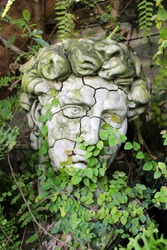 A cracked face garden ornament with green moss and plant growth creeping onto the statue's head.