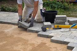 A craftsman lays concrete paving stone blocks on sand.