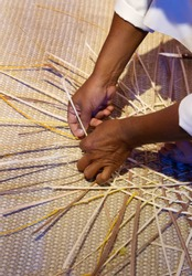 A craftsman weaving a baskets from palm leaves