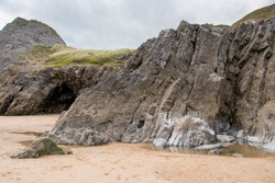 A craggy little cave opening in the cliff face at Three Cliffs Bay, The Gower Peninsula, Wales
