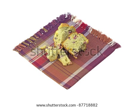 A cranberry and orange baked muffin broken apart with pieces on a cloth napkin. - stock photo